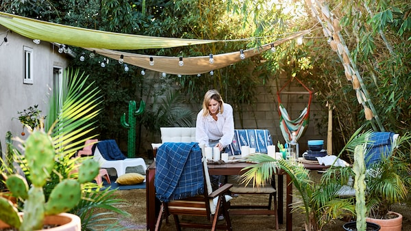 Chloé setting the table outside in her garden, with wooden furniture, plants, trees and canopies with light chains.