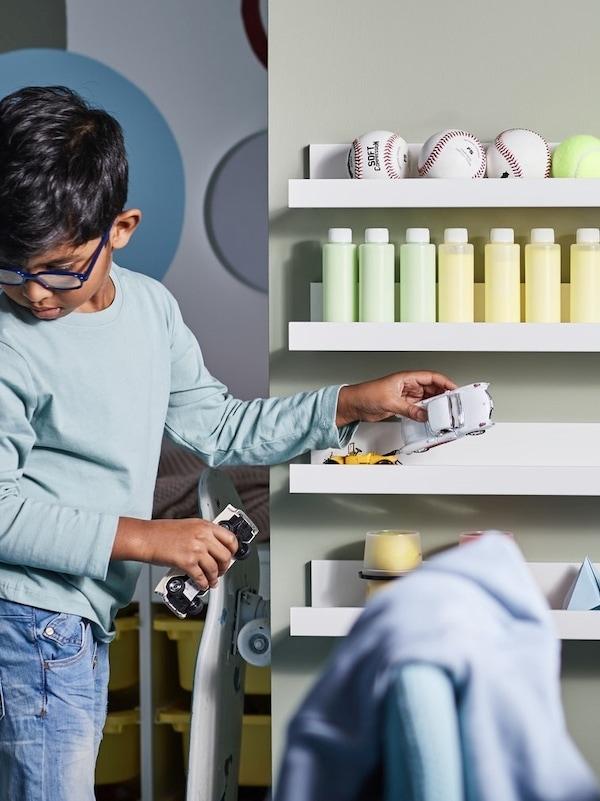 Chłopiec porządkujący piłki, butelki, zabawki, papierowe modele i samochodziki na czterech białych półkach na zdjęcia MOSSLANDY zamontowanych na ścianie.