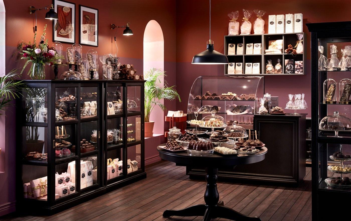 Chocolataria com armários MALSJÖ da IKEA em velatura preta com portas de vidro e paredes em castanho, que expõem diversas guloseimas embrulhadas.