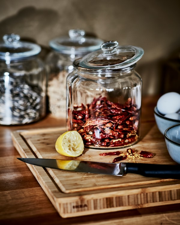 Chopped, dried chillies on a butcher's block in bamboo, a knife, a squeezed lemon and a glass jar with more dried chillies.