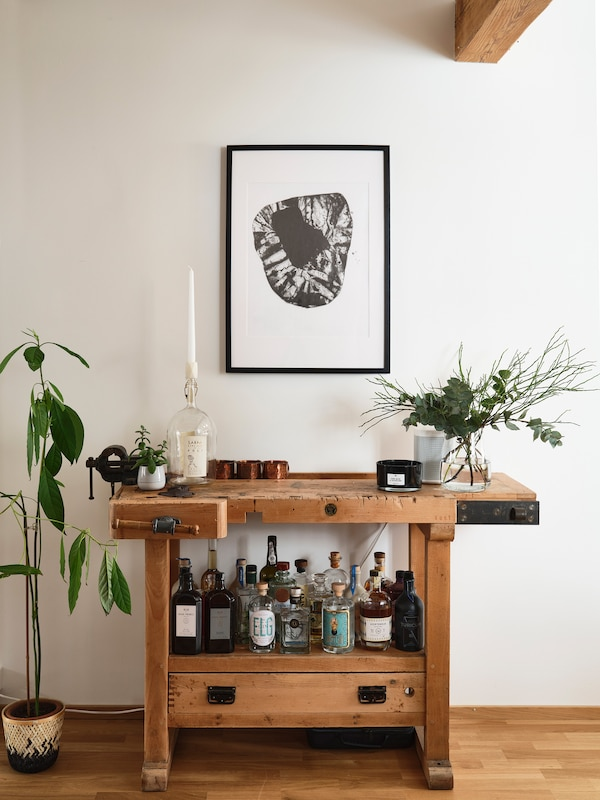 Chris's grandfather's wooden workbench is now used to store his gin collection.