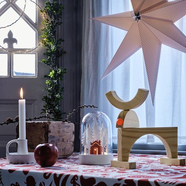 Christmas table with candles, decorative lights and a pendant star lamp.