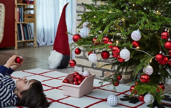 Christmas tree heavy with decorations with a young boy lying face up on rug next to it, inspecting an ornament.