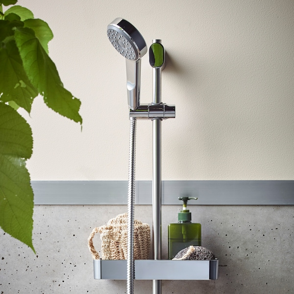 Chrome-plated, BROGRUND riser rail with handshower kit, mounted on a wall with a tray that holds a sponge and soap dispenser.