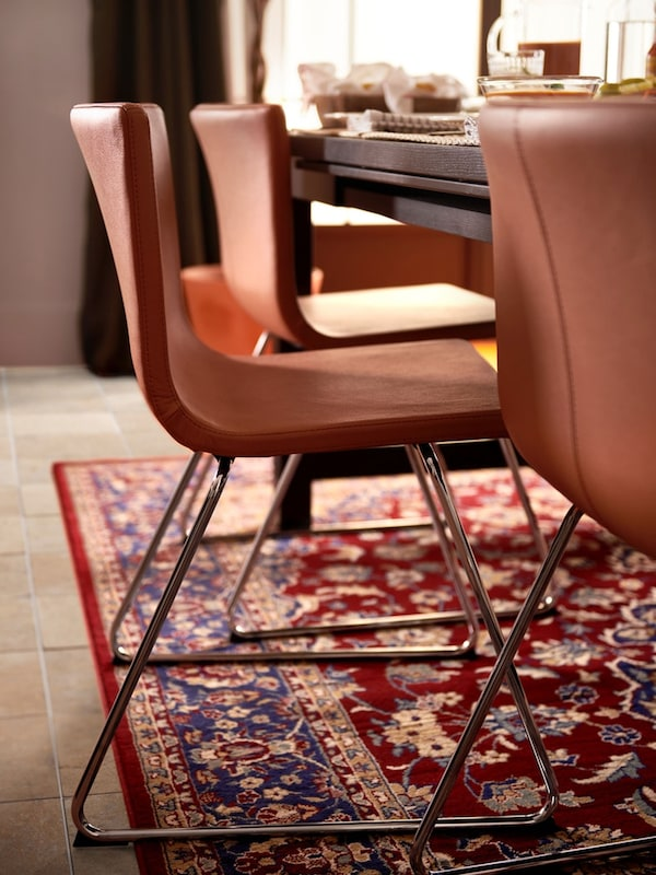 Chrome plated Mjuk golden brown BERNHARD chair in warm dining room setting
