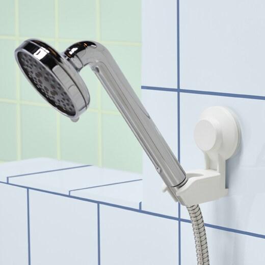 Chuveiro prateado em suporte para chuveiro com ventosa branco numa parede de azulejo.