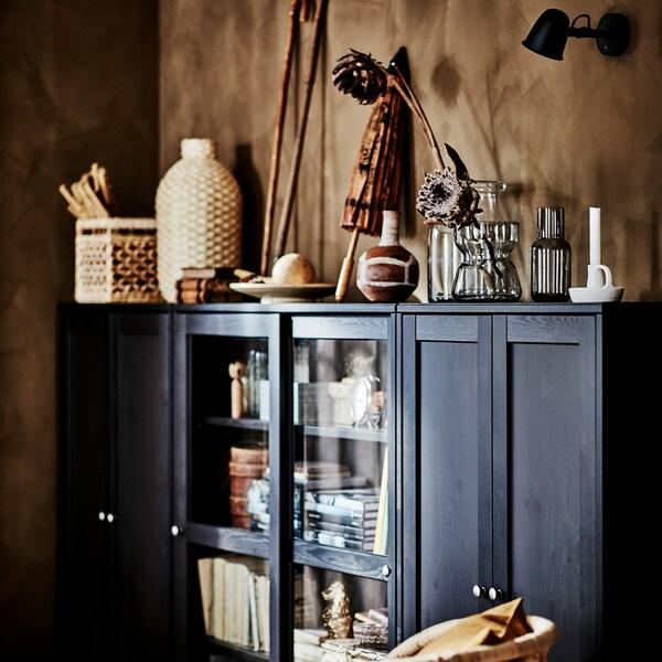 Ciemnobrązowa szafka z przeszklonymi drzwiami z mnóstwem książek i wykonanych z naturalnych materiałów ozdób w naturalnych kolorach.