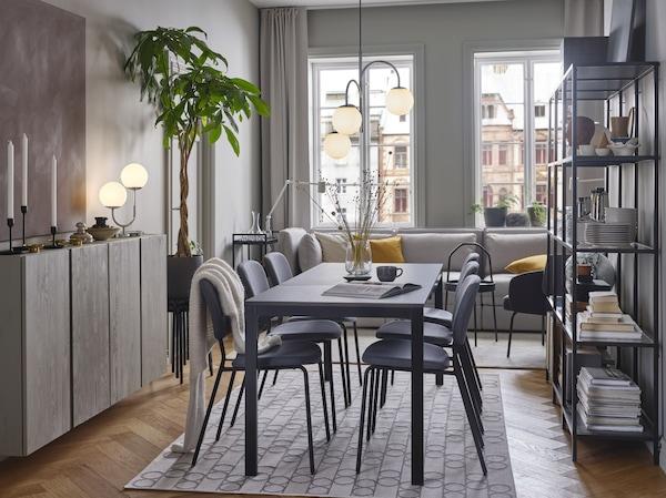 Ciemnobrązowy stół i szare krzesła ustawione na dywanie w geometryczne wzory. Nad nimi wisi trójramienna, chromowana lampa.