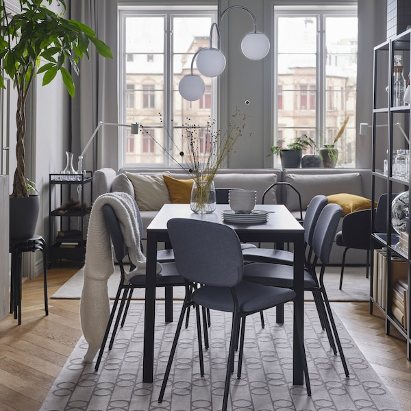Ciemnobrązowy stół, szare krzesła, dywan w geometryczne wzory, chromowana lampa wisząca z białymi kloszami i jasnoszara sofa.