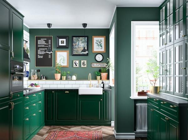 Ciemnozielona kuchnia z białymi płytkami, mosiężna baterią i ścianą obrazów w różnych ramach.