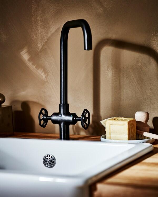 Čierna kovová kuchynská batéria, biely drez, pracovná doska z dubovej dyhy a drevená kefka na riad.