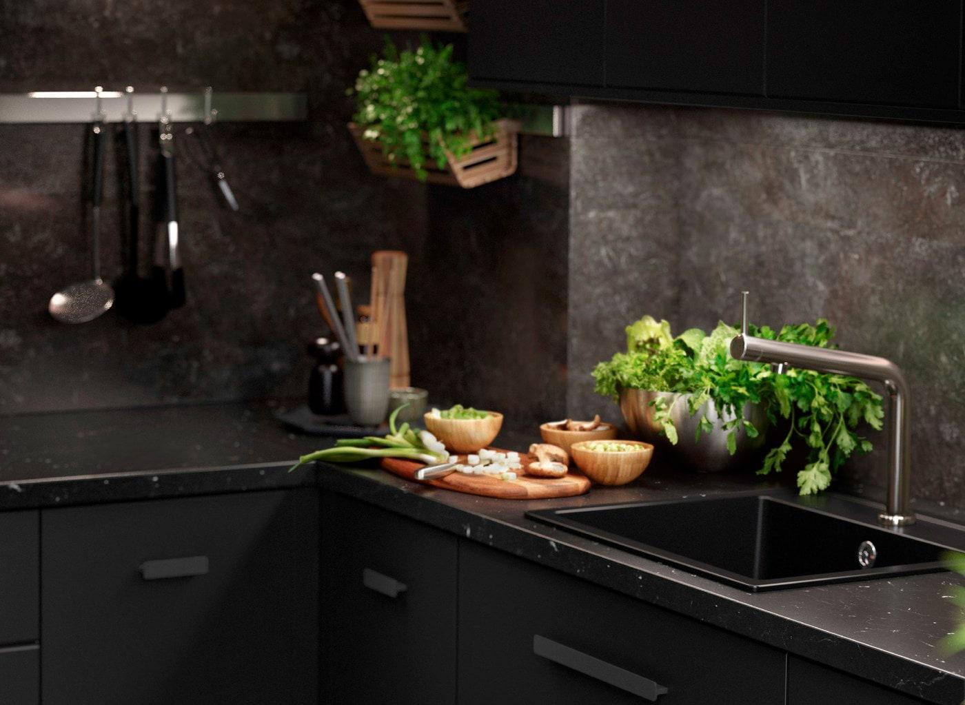 Čierna kuchyňa KUNGSBACKA s prvkami so vzorom mramoru, v ktorej je kuchynské náčinie a čerstvé bylinky.