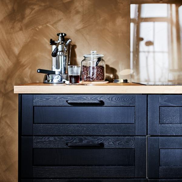 Čierna spodná skrinka s čiernymi čelami zásuviek a drevenou pracovnou doskou, na ktorej je kávovar a dóza s kávou.
