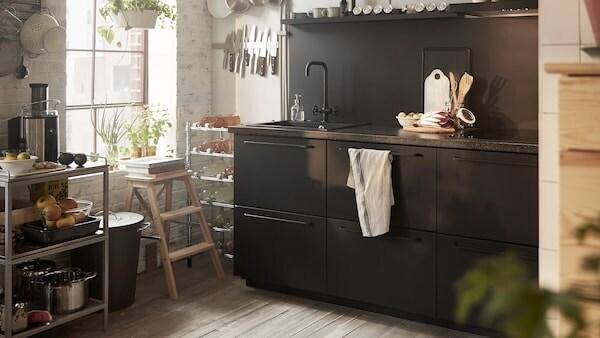 Čierne kuchynské skrinky s drezom, kovový vozík a kuchynské náčinie na lište pri okne.
