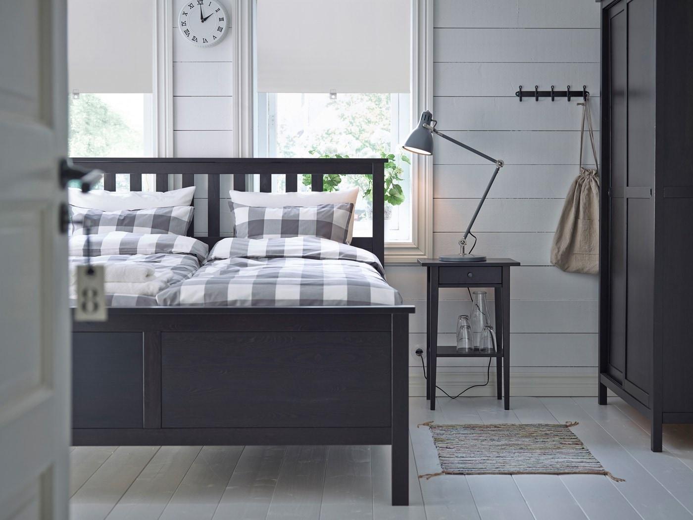 Čiernohnedý rám postele IKEA HEMNES s posteľnými obliečkami so sivo-bielym károvaným vzorom v malej spálni.