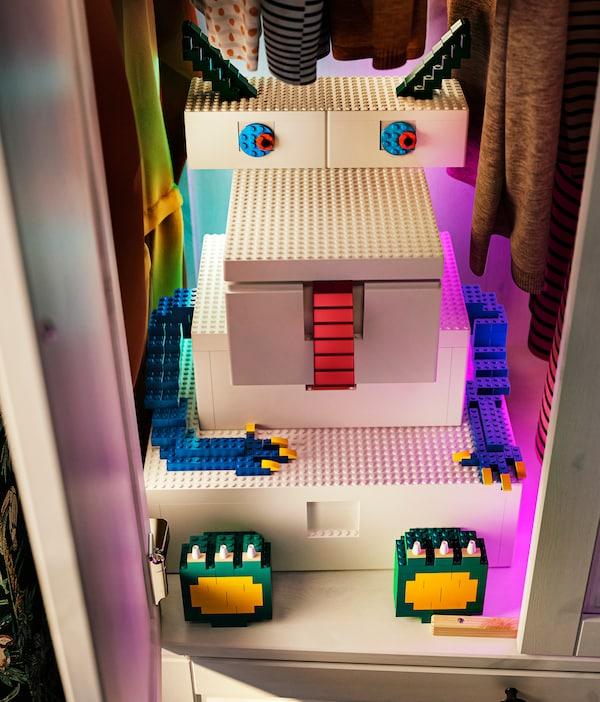 Cinq boîtes BYGGLEK blanches de différentes tailles sont placées pour former un monstre, avec des briques LEGO ajoutées pour définir ses traits.