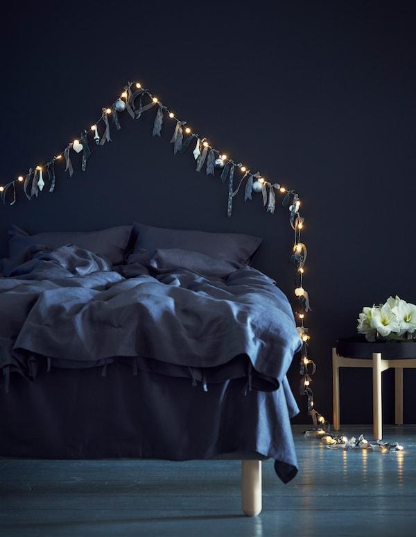 Cintas y adornos atados a una guirnalda luminosa y clavados en una pared, sobre una cama.