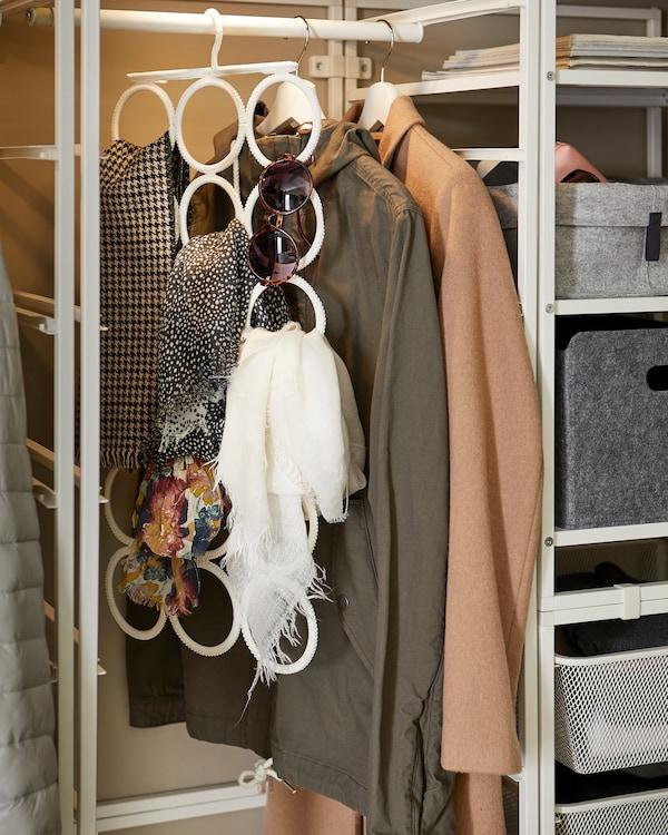 Cintre multi-support IKEA KOMPLEMENT en blanc garni de lunettes de soleil et de foulards, et accroché à une tringle à vêtements.