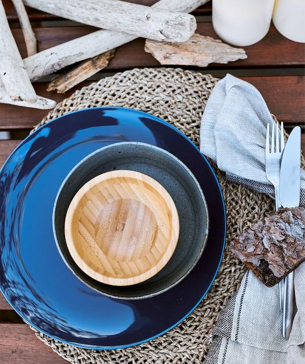 Ciotole in legno e ceramica blu con una tovaglietta intrecciata su una tavola decorata con rami - IKEA