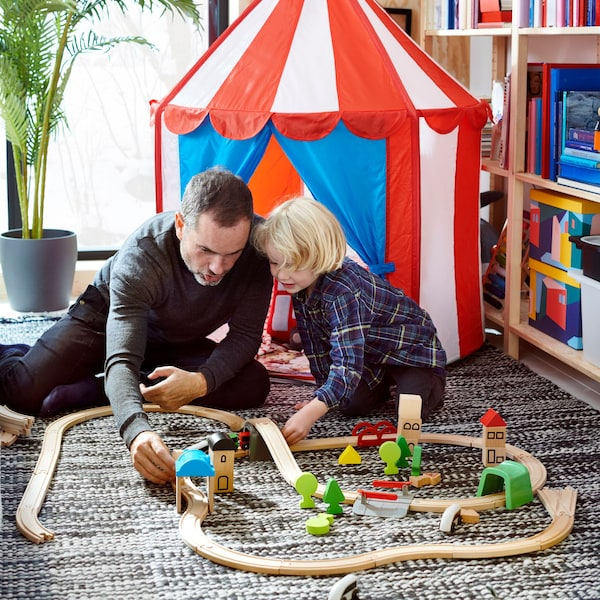 CIRKUSTÄLT sátor előtt apa és fia LILLABO vonatpályát épít.