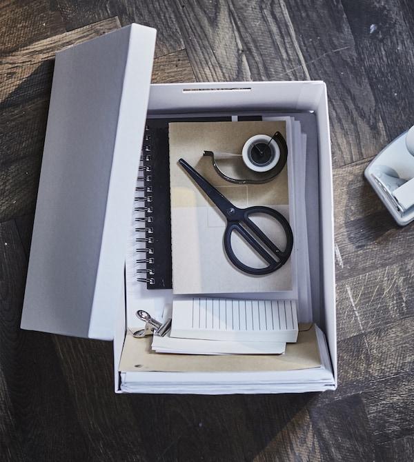 Ciseaux, papiers, ruban adhésif et autres fournitures de bureau trouvent leur place dans les boîtes de rangement à poignées intégrées.