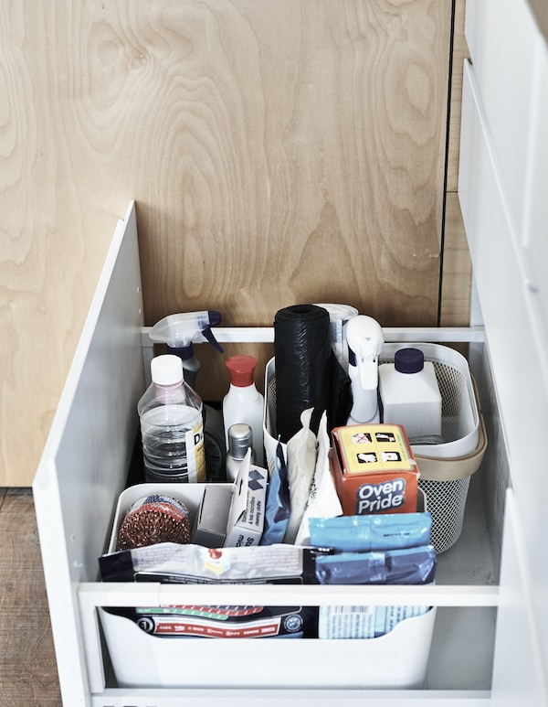Cleaning products stored in boxes inside a drawer.