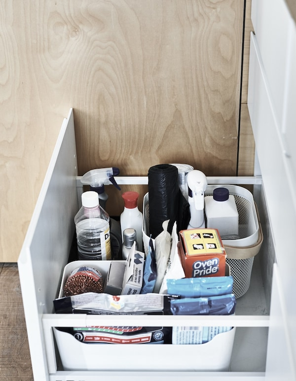 Cleaning products stored in boxes inside a open kitchen drawer.
