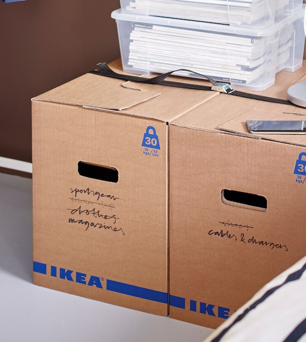 Clear containers filled with paper, placed on top of JÄTTENE boxes with various writings on them.
