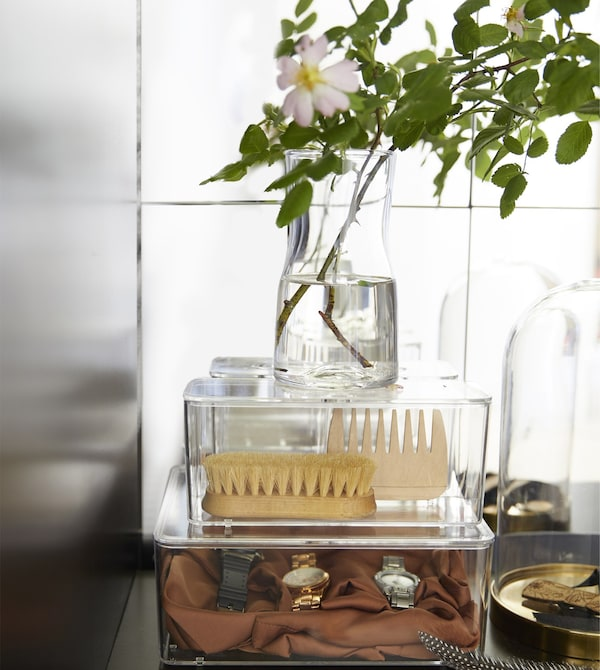 Clear storage boxes organise personal grooming items on a bedroom vanity.