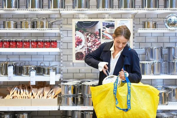 Cliente mujer compra ollas en la parte de Decohogar de la tienda IKEA con su bolsa amarilla y azul.