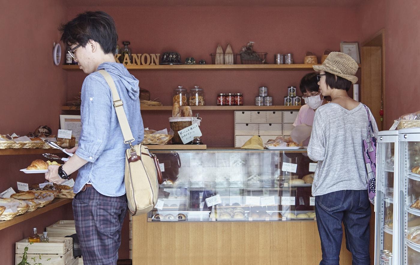 Clients en train de choisir des pains et des gâteaux dans la boulangerie.