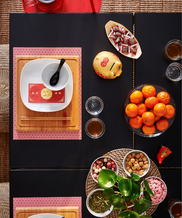 Close-up image of a table place setting with a red GALLRA place mat and food dishes.