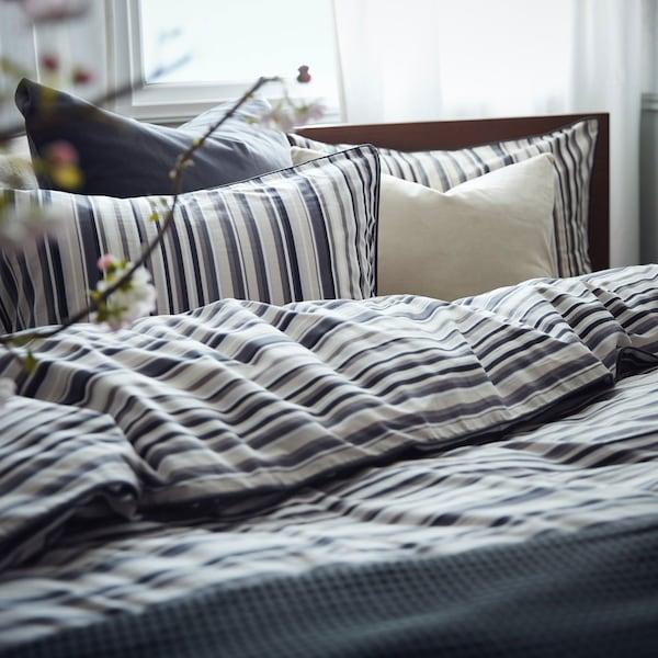 Close up image of striped bedding set in natural lit bedroom