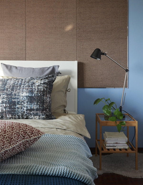 Close-up of a bed and bedside table against a blue wall.