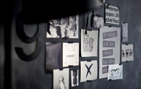 Close-up of a black-and-white inspiration board art wall with removable tape.