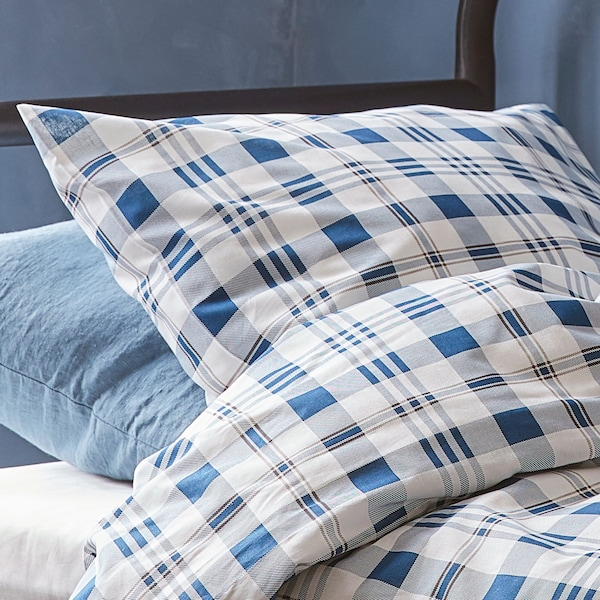 Close up of a blue plaid duvet cover and pillow.