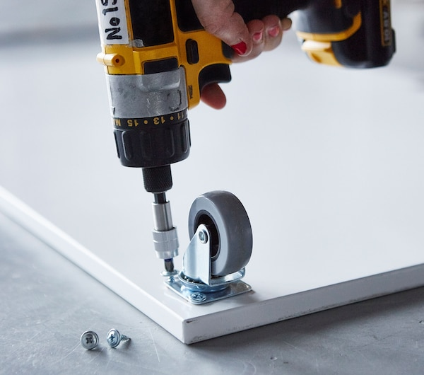 Close-up of a castor being attached to a board.
