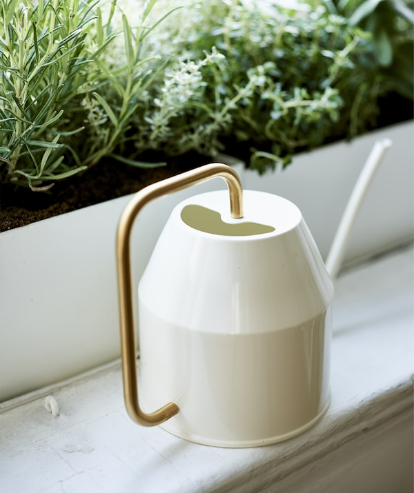 Close-up of a cream and gold watering can on a windowsill.