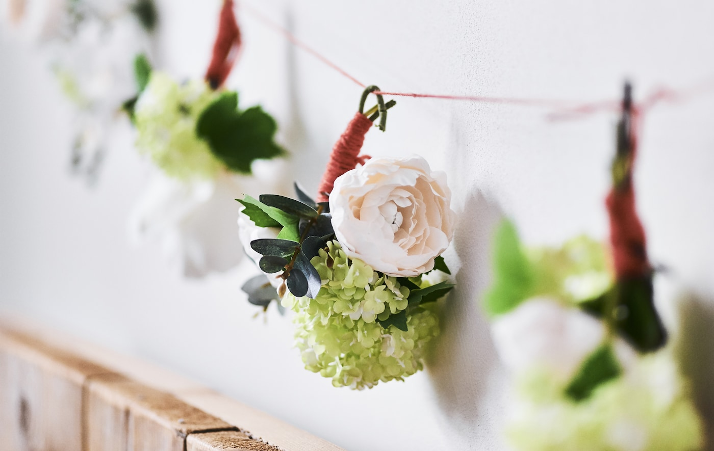 Close-up of a floral garland on a white wall.