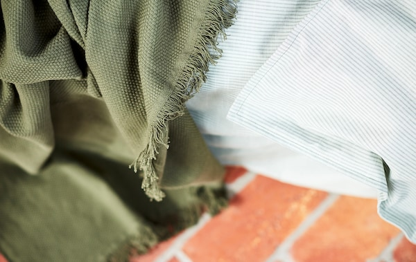 Close-up of a green blanket and a light grey striped fabric, shown against a red stone floor.