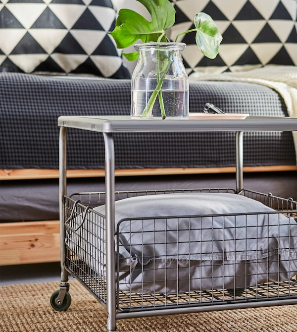 Close-up of a grey steel coffee table with a wire mesh basket underneath.
