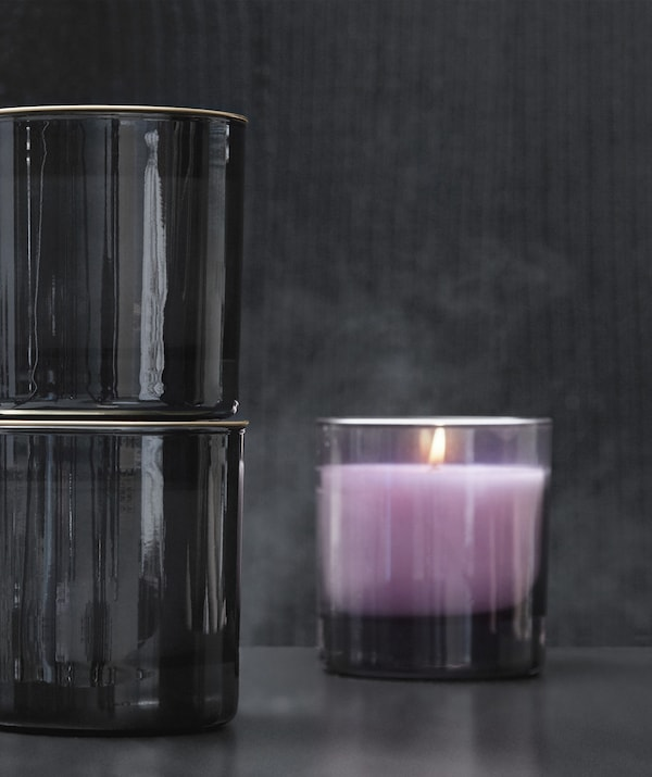 Close-up of a lavender-coloured candle in a smoked-glass holder, against a dark grey background.