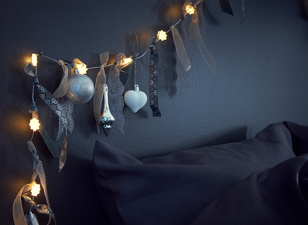 Close-up of a light chain decorated with ribbons, strips of fabric and baubles above a bed.