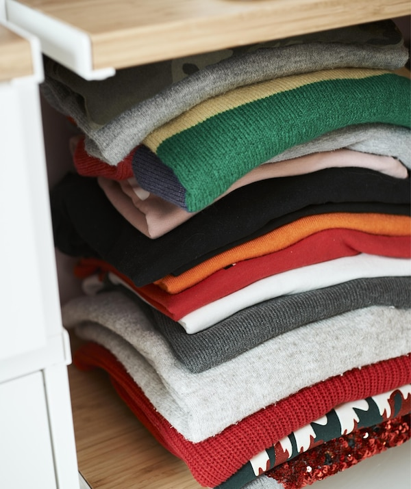 Close up of a pile of colourful folded knitwear on a shelf.