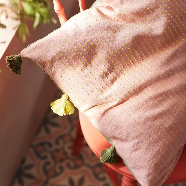 Close up of a pink textured cushion with multicoloured tassels.