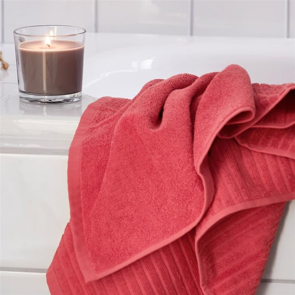 Close up of a pink towel and a grey candle