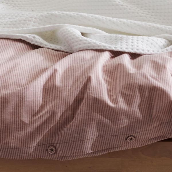 Close up of a red and white pinstriped duvet cover with button details.