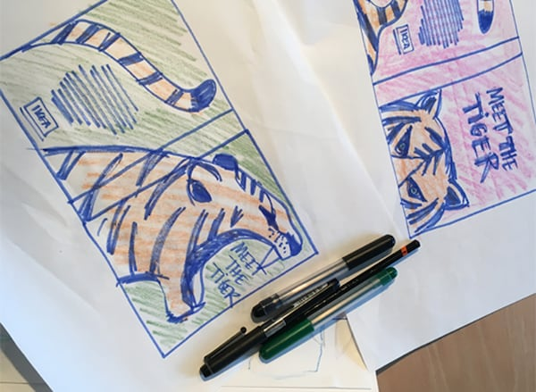 Close-up of a sketch of a tiger and some pens.