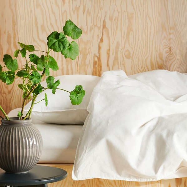 Close up of a white duvet and pillow, with a plant in the foreground.