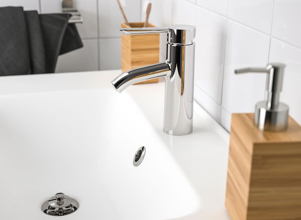 Close-up of a white sink with a chrome plated faucet, with a bamboo soap dispenser.